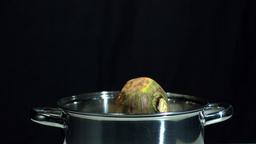 Turnip falling in saucepan on black background Footage