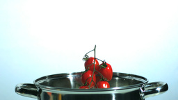 Vine tomatoes and parsnip falling in saucepan Footage