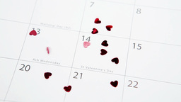 Heart confetti falling on calendar on highlighting valentines day Live Action