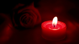 Candle Flickering Beside Red Roses And Going Out stock footage