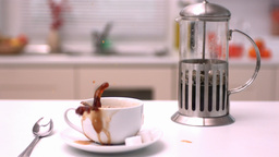 Sugar cube falling in coffee cup in kitchen Footage