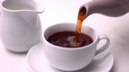 Tea being poured into cup by teapot Stock Video Footage