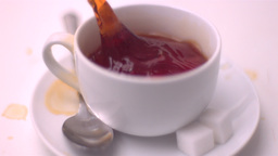 Sugar cube falling into tea and splashing Footage