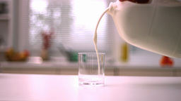 Milk pouring into small glass in kitchen Stock Video Footage