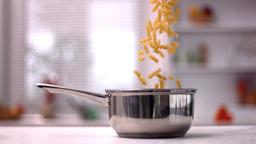 Fusilli falling in saucepan in kitchen Stock Video Footage