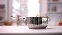 Fusilli falling into a saucepan in kitchen Stock Video Footage
