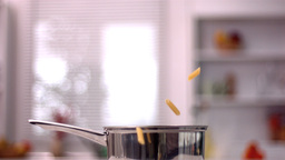 Penne falling into pot in kitchen Stock Video Footage