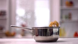Tagliatelle falling in pot in kitchen Footage