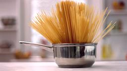 Spaghetti in a saucepan in kitchen Footage