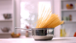 Spaghetti falling in saucepan in kitchen Footage