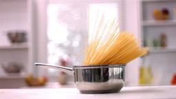 Spaghetti falling in saucepan in kitchen Footage