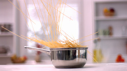 Spaghetti falling into pot in kitchen Footage