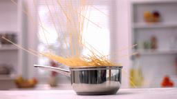 Spaghetti falling into pot in kitchen Footage