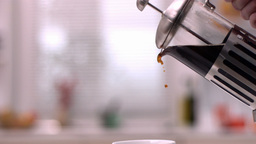 Cafetiere pouring coffee into cup Footage