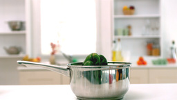 Green pepper falling in saucepan in kitchen Footage