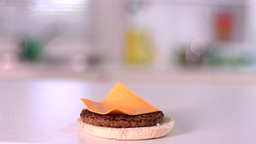 Cheese Falling On Bun Burger In Kitchen stock footage