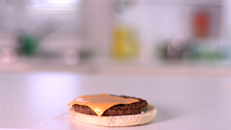 Slice of cheese falling on bun burger in kitchen Stock Video Footage