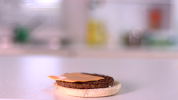 Slice Of Cheese Falling On Bun Burger In Kitchen stock footage