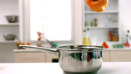 Yellow pepper falling in saucepan in kitchen Stock Video Footage