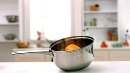 Yellow pepper falling in saucepan in kitchen Footage