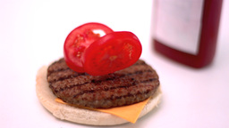 Sliced tomatoes falling on burger in kitchen Footage