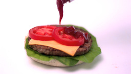 Ketchup pouring onto burger on white background Stock Video Footage