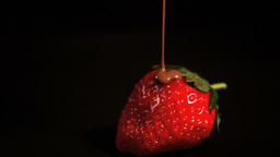 Melted chocolate pouring over strawberry Footage