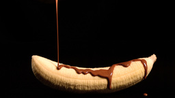 Melted chocolate pouring over a banana Stock Video Footage