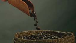 Hand pouring coffee beans from wooden spoon into b Footage