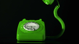 Receiver falling on green dial phone on black back Footage