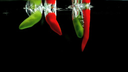 Chili peppers falling in water Stock Video Footage