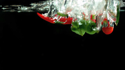 Red and green chili peppers falling in water Stock Video Footage