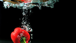 Red pepper falling into water and floating Footage