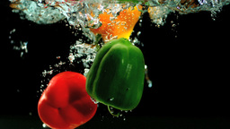 Three peppers falling in water and floating Footage