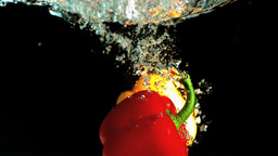 Yellow and red peppers falling into water and floa Footage