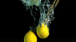 Two lemons dropping in water Stock Video Footage