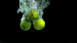 Three limes dropping into water Footage
