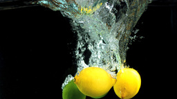 Lemons and limes dropping in water Stock Video Footage