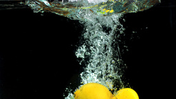 Lemons and limes dropping in water Footage