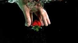 Hand taking strawberry from water Footage