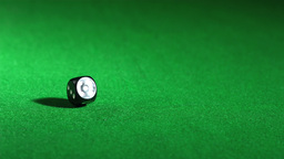 Black dice falling on green table and spinning Stock Video Footage