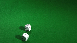 White dice rolling over a green table Footage