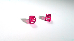 Pink dice rolling on white surface Stock Video Footage