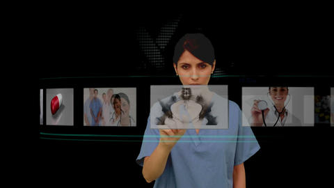 Nurse using digital interface to look at various x Stock Video Footage