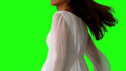 Girl in white dress twirling on green screen close Footage