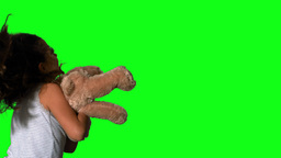 Little girl twirling and holding teddy on green sc Stock Video Footage