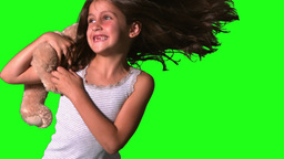 Little girl twirling and catching teddy on green s Footage