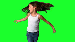 Little girl spinning around on green screen Footage