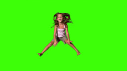 Happy girl jumping up and down on green screen Footage