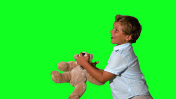 Little boy jumping and catching teddy on green scr Stock Video Footage